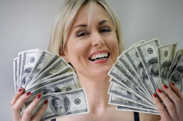 Happy Woman Fanning Out Money --- Image by © Steve Prezant/Corbis